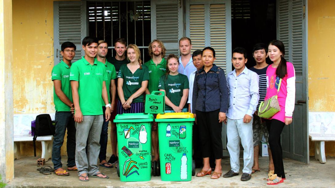 Personal y voluntarios en Camboya posando con los contenedores de reciclaje en una escuela local.